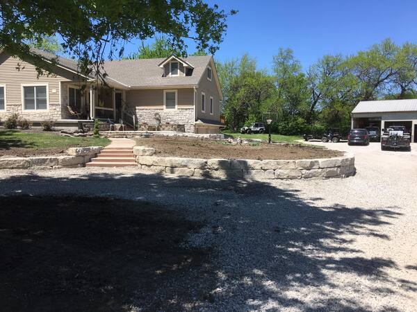 Retaining wall forming natural areas near gravel driveway