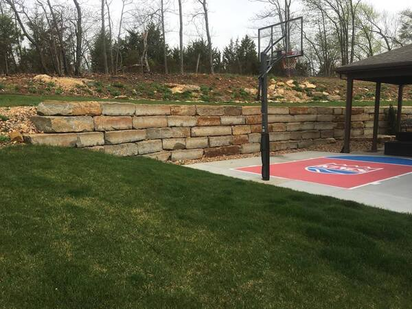 Retaining wall framing a seating area in a backyard with a half basketball court