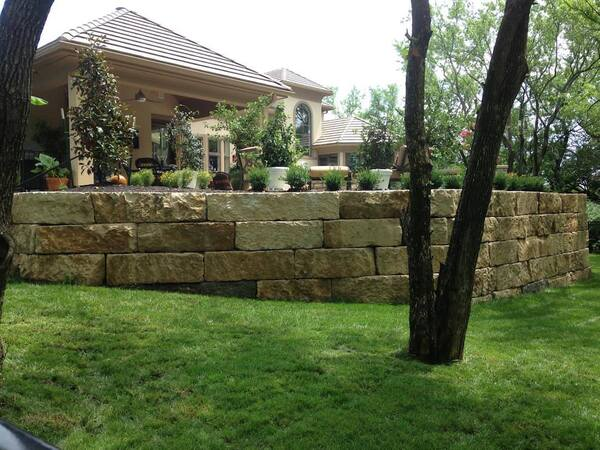 Stone retaining wall helping create natural area by a patio