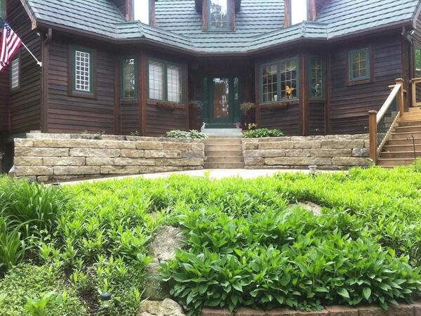 Stone retaining walls create small natural areas by the front door