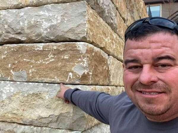 Bob Kerr with a newly built stone retaining wall